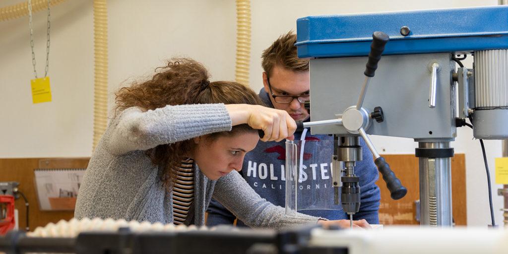 Remo, angehender Holzbauingenieur und Lorena, Architekturstudentin, arbeiten konzentriert in der Werkstatt.